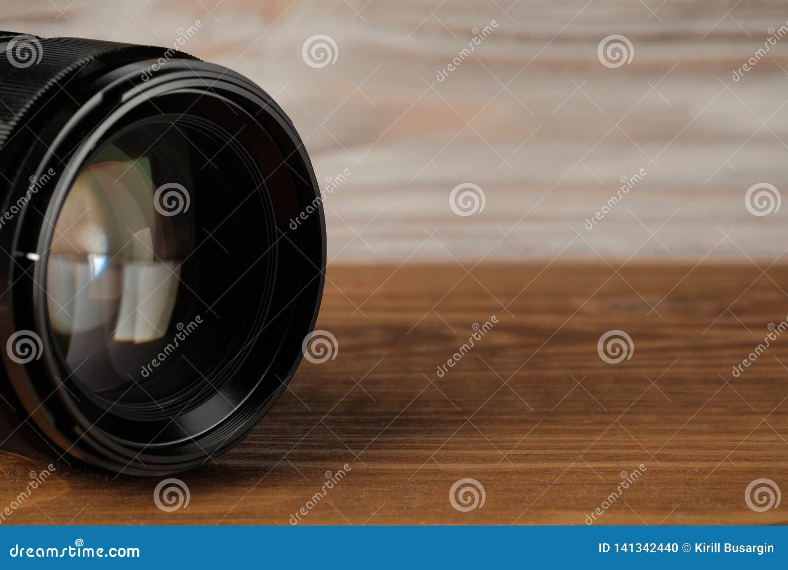 Lente de la foto de la cámara en la tabla de madera vieja