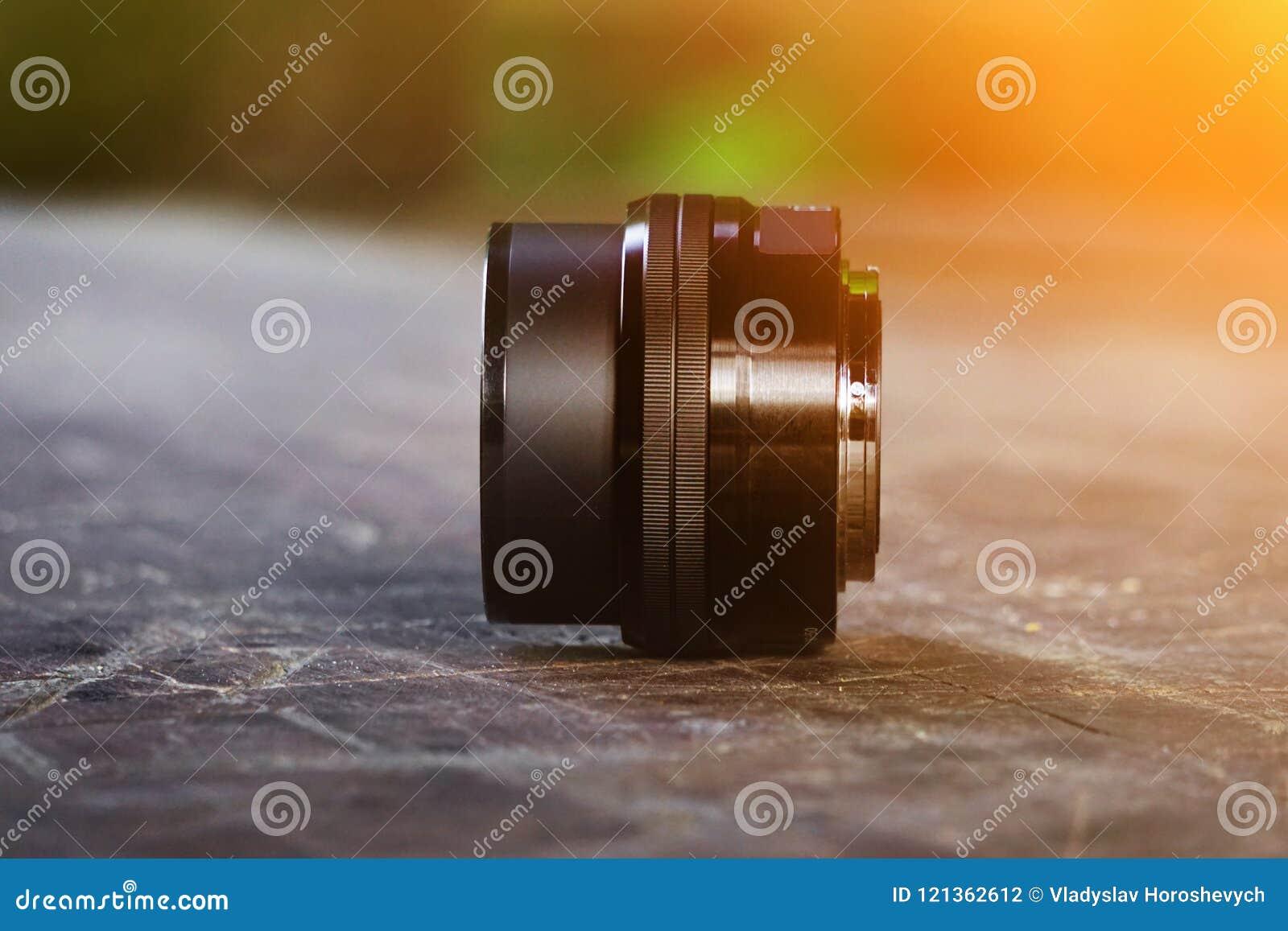 Lente para a câmera, em uma mesa de madeira velha, lente preta, fotógrafo