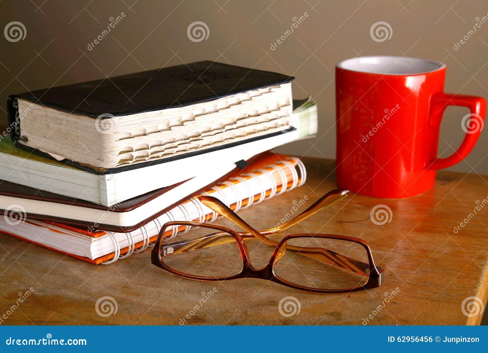 Lentes, taza de café y pila de libros