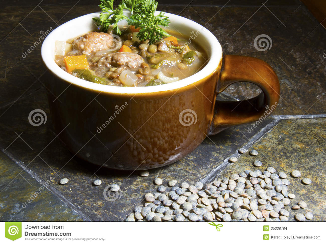 ... italian sausage and lentil soup on slate table with green lentils and