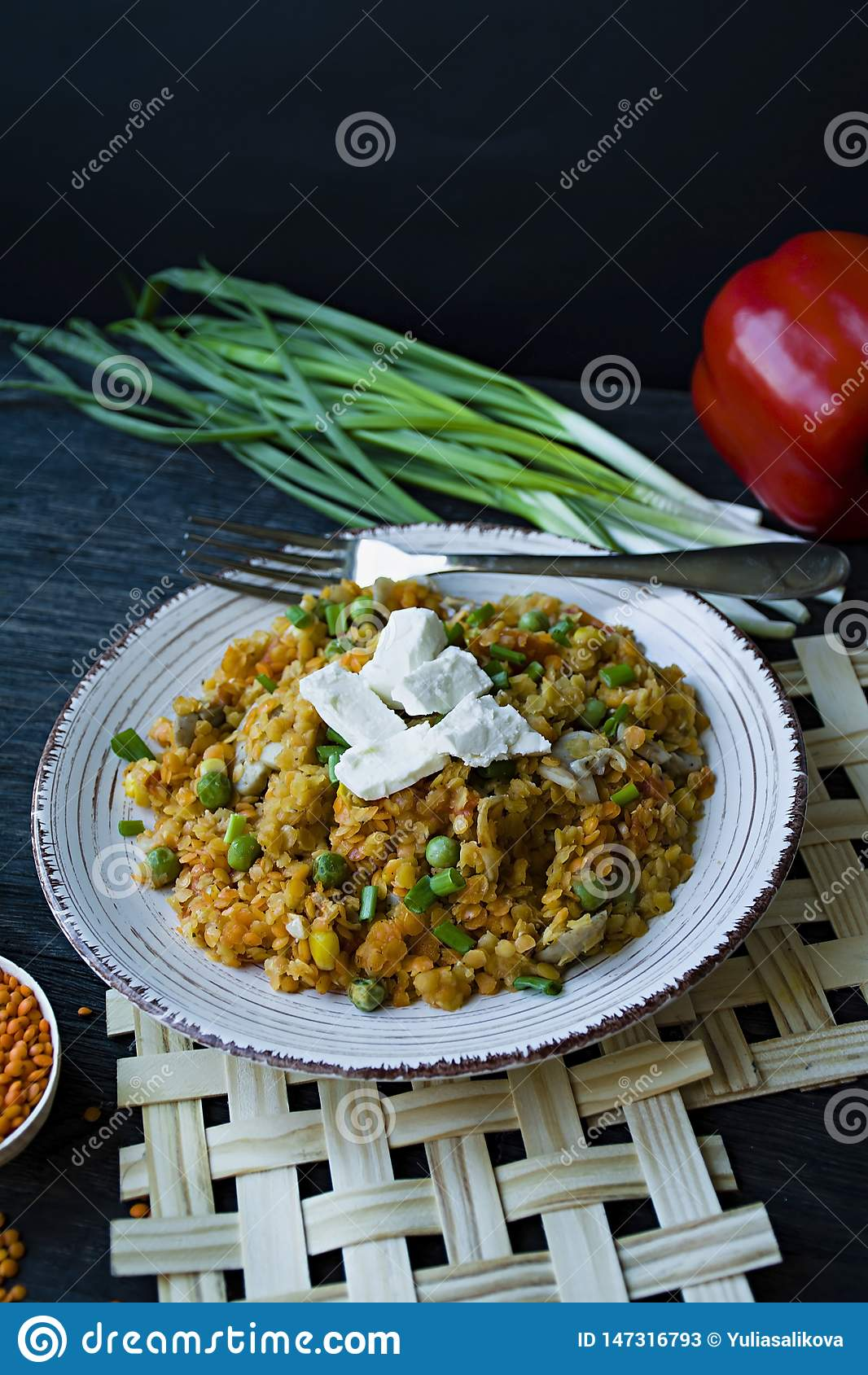 Lentil porridge with vegetables and herbs and fett cheese. Healthy lifestyle. Dietary menu. Dark wooden background. Side view