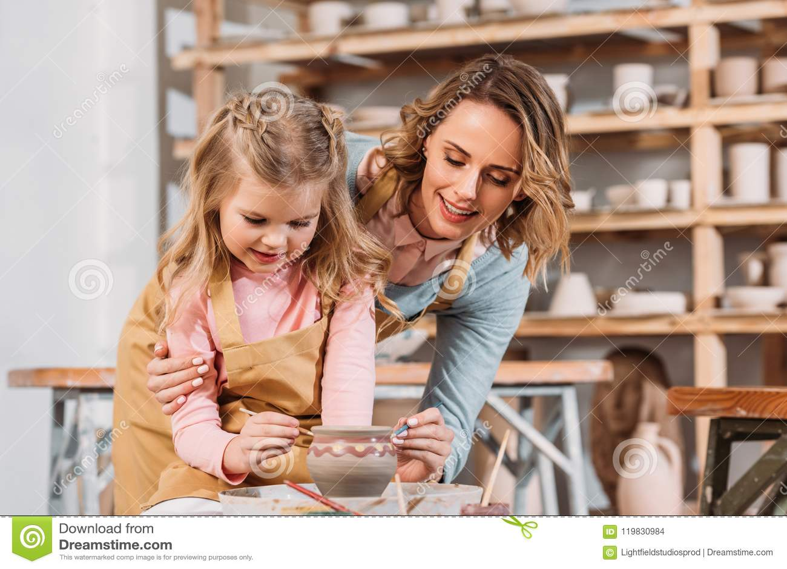 Leraar en jong geitje die ceramische pot schilderen