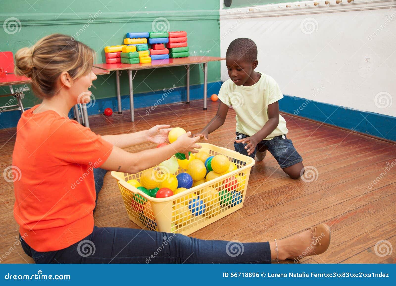 Leraar het spelen met een kleine student