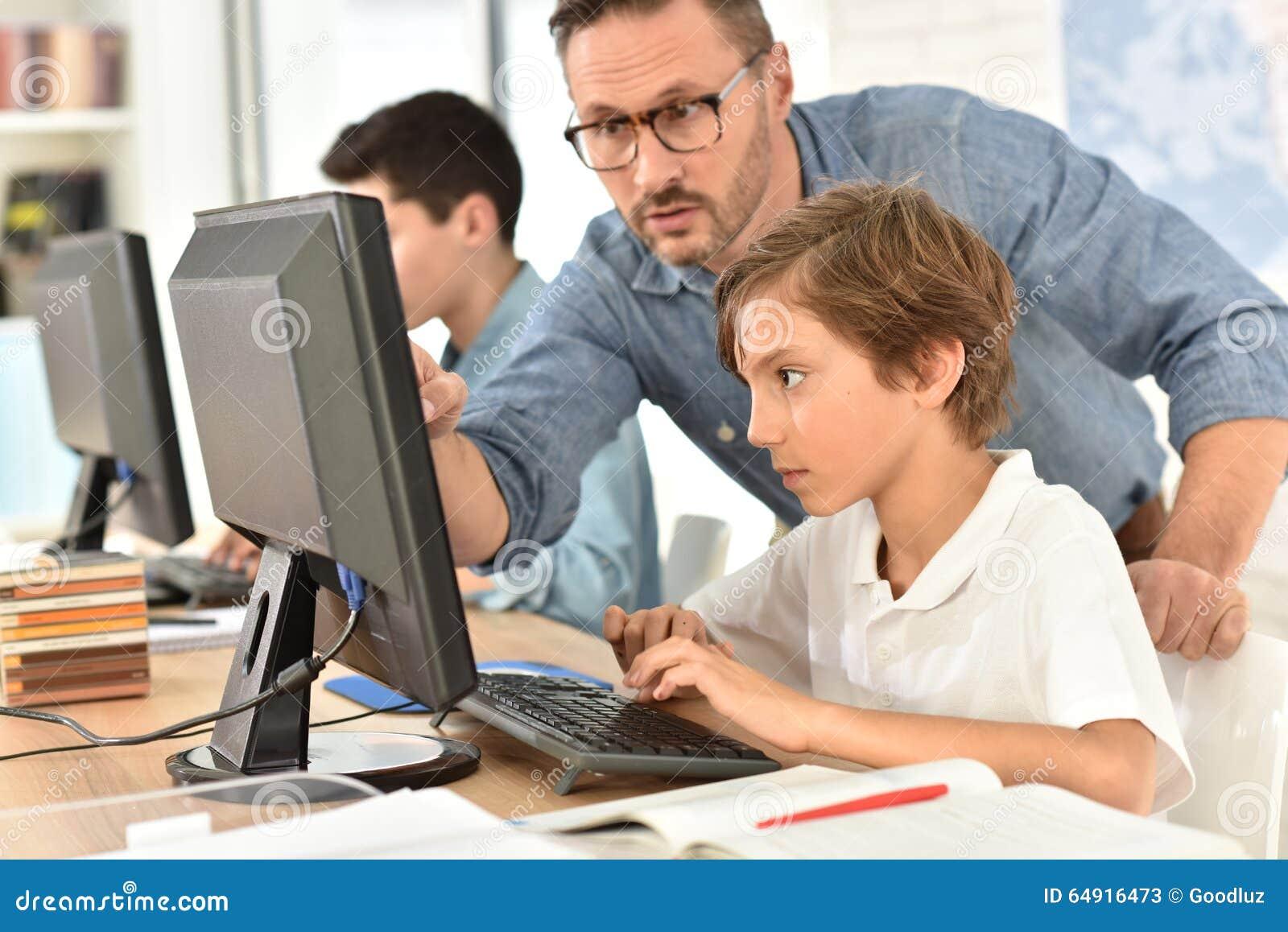 Leraar met kinderen in de gegevensverwerking van klasse