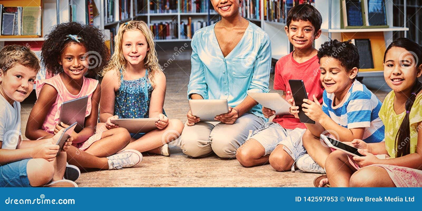 Leraar met kinderen die digitale tabletten houden