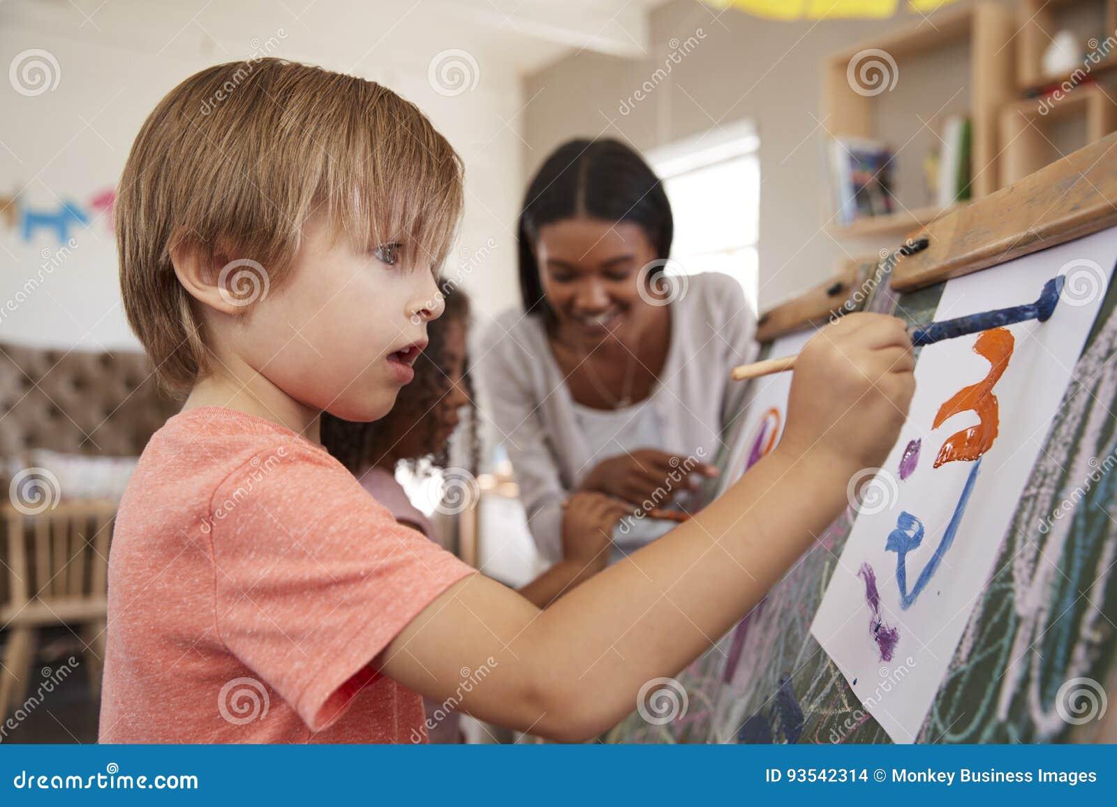 Leraar At Montessori School die Kinderen in Art Class helpen