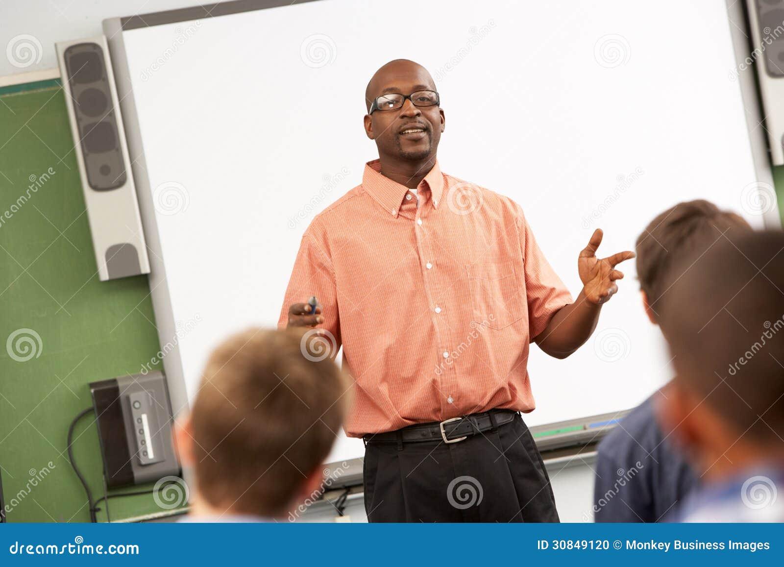 Leraar Talking To Class die zich in Front Of Whiteboard bevinden