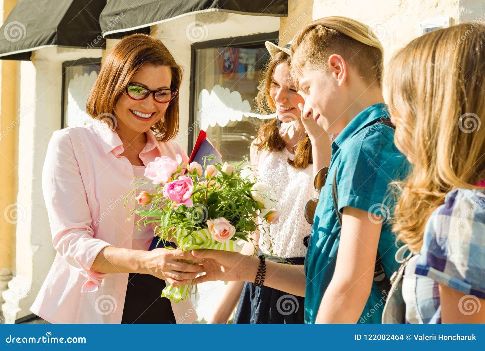 Leraars` s Dag, openluchtportret van gelukkige midden oude vrouwelijke middelbare schoolleraar met boeket van bloemen en groepsst
