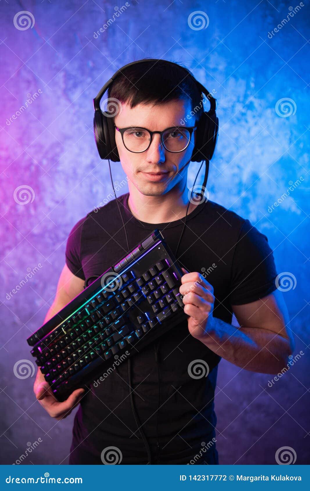 Lerdo do computador com o teclado sobre o rosa colorido e a parede leve de néon azul
