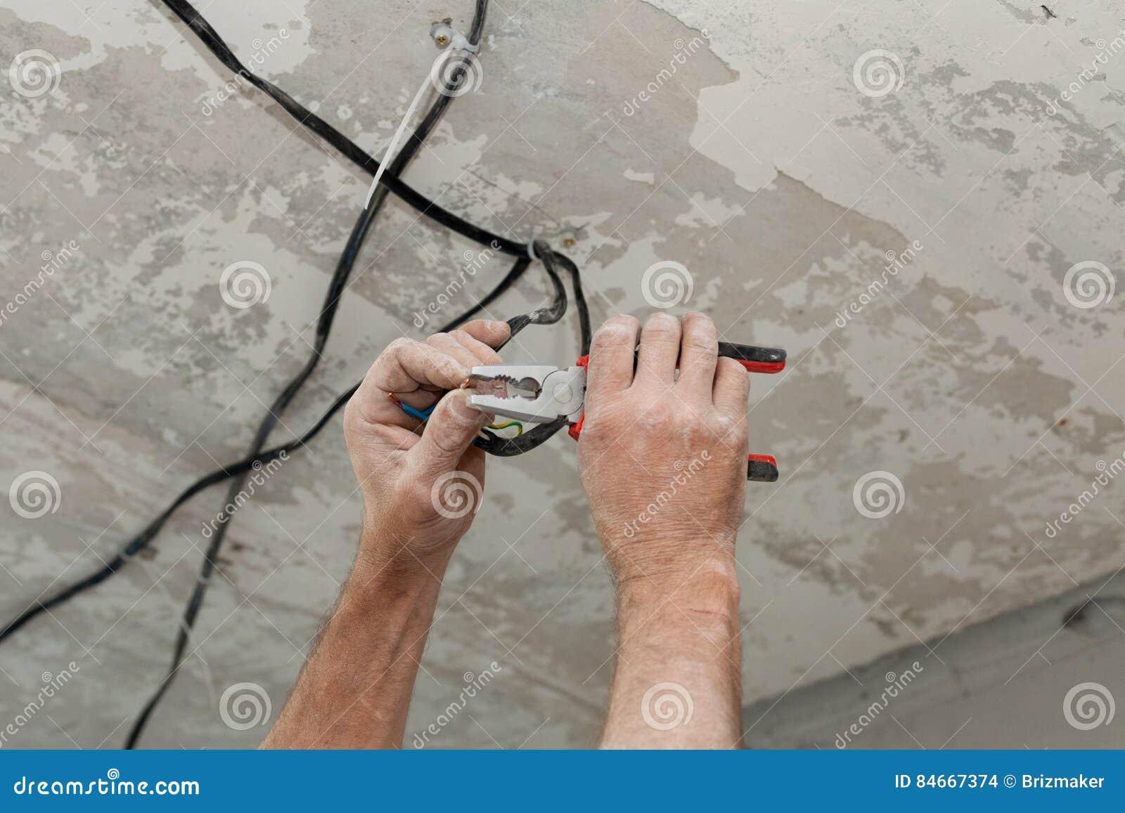 Les électriciens nettoie les contacts avec des pinces Installation du plafonnier