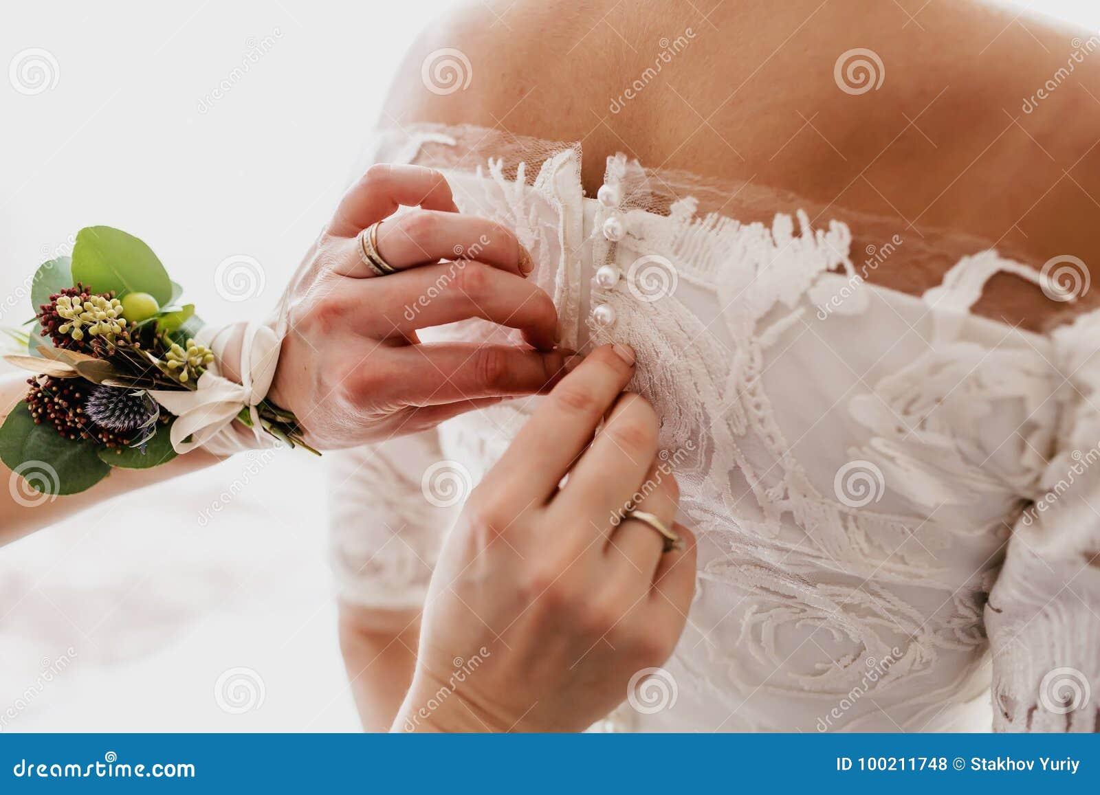 Les aides de mère attachent une robe de mariage la jeune mariée avant la cérémonie Proue d étoile bleue avec la bande bleue (enve