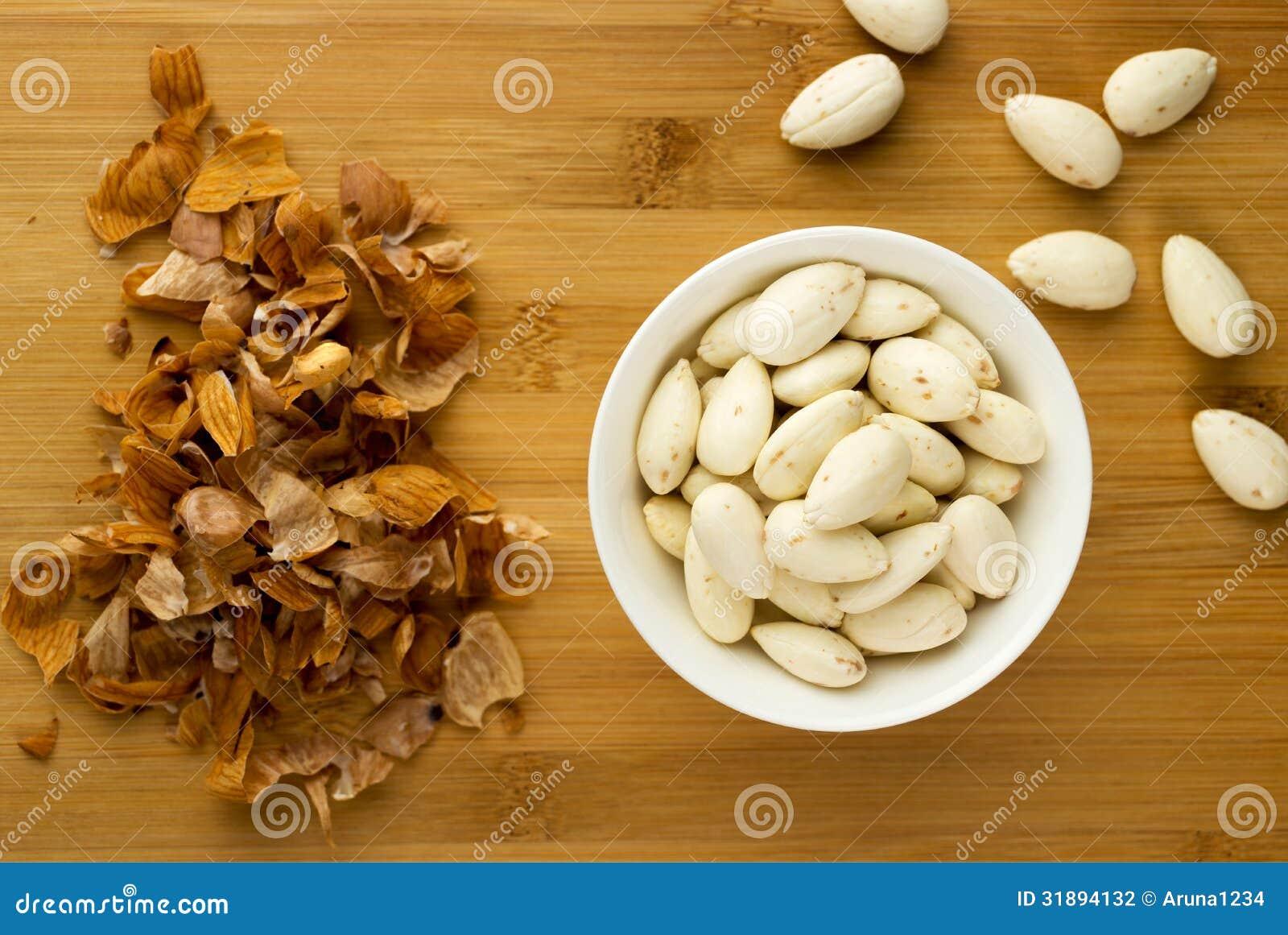 Les amandes blanchies dans une cuvette à côté d amande épluche