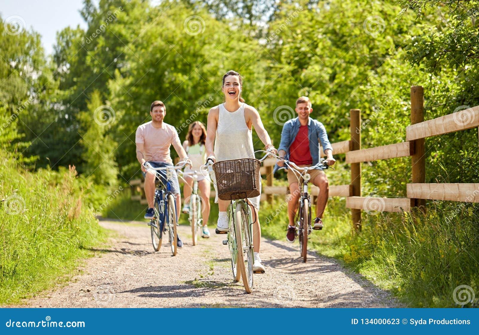 Les amis heureux montant la vitesse fixe va à vélo en été