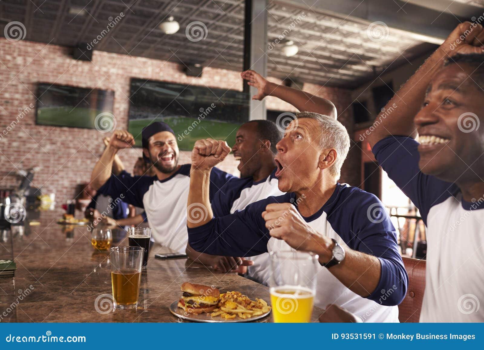Les amis masculins dans le jeu de montre de barre de sports et célèbrent