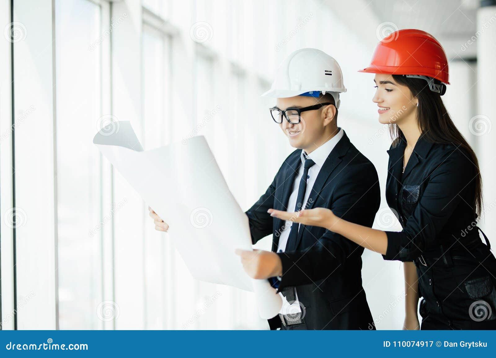 Les architectes d homme d affaires regardent l architecte de papier de femme d affaires de plan dans le bureau pour discuter des