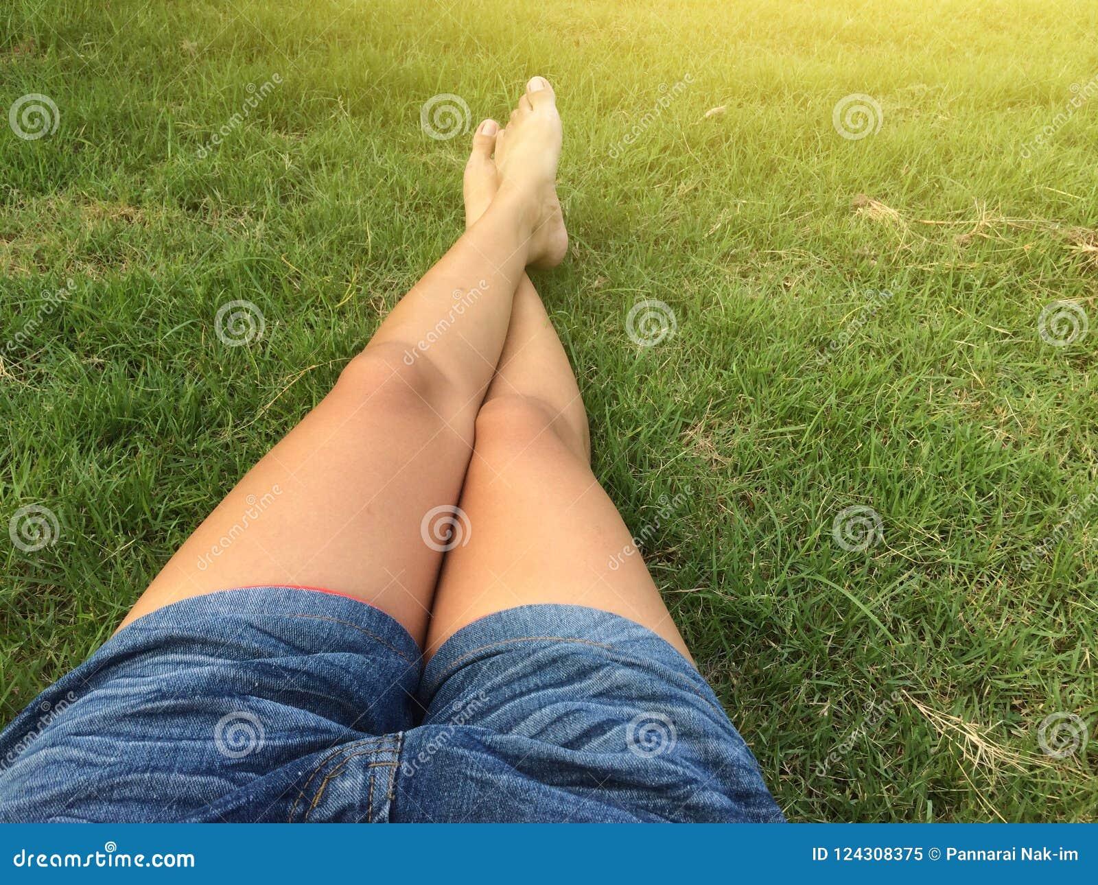 Les articles de femme court-circuitent le treillis se reposant sur l herbe verte