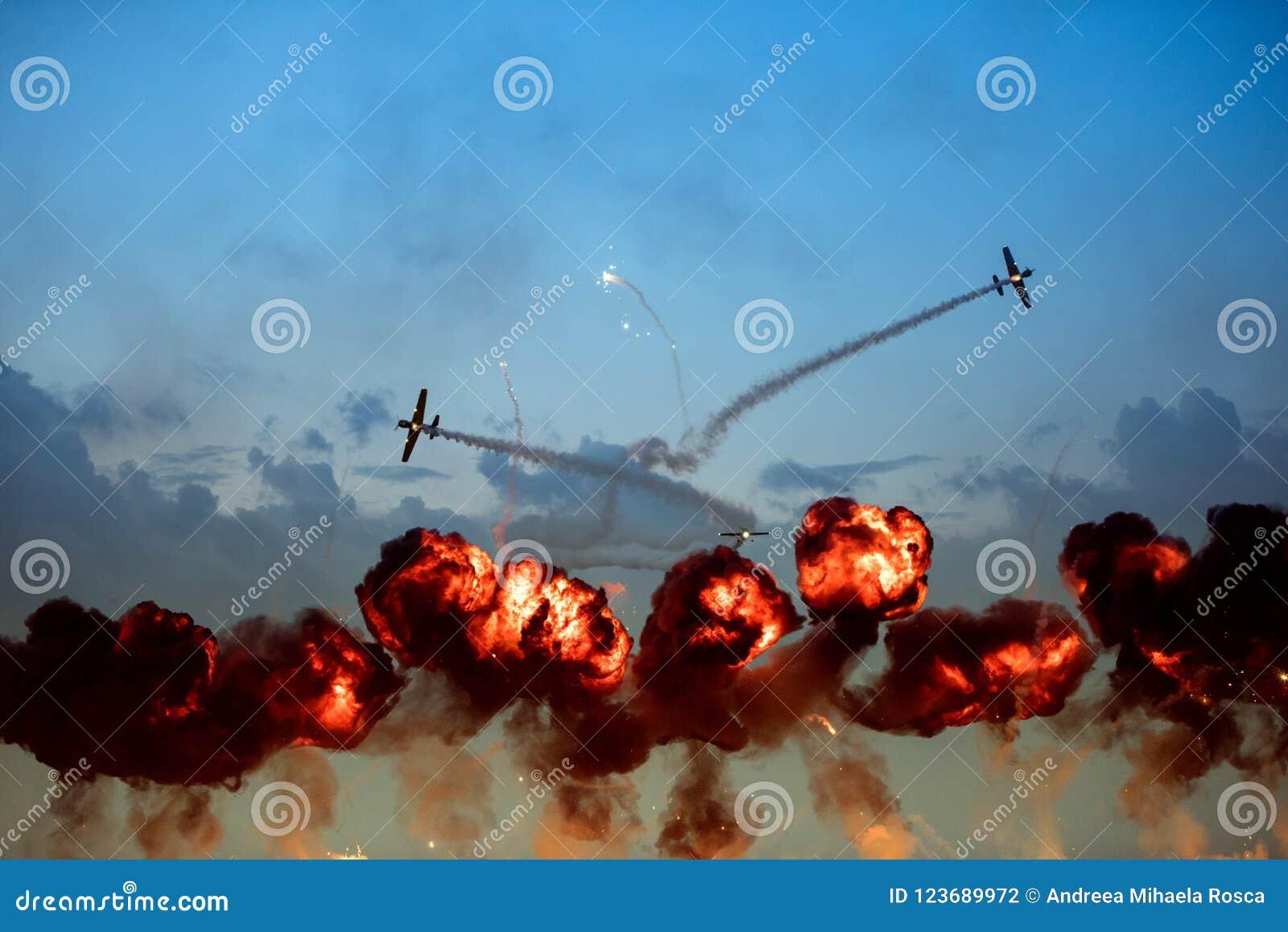 Les avions faisant des tours pendant les flammes explosives puissantes montent
