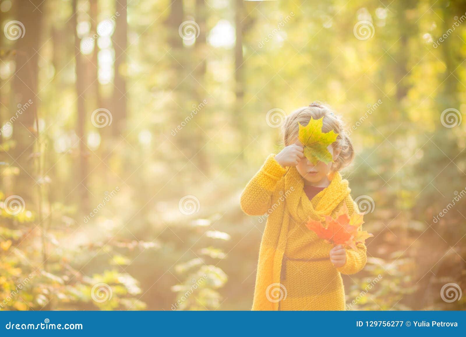 Les belles 5 années de fille blonde cache son visage derrière une feuille d érable sur un fond de forestAutumn ensoleillé d autom
