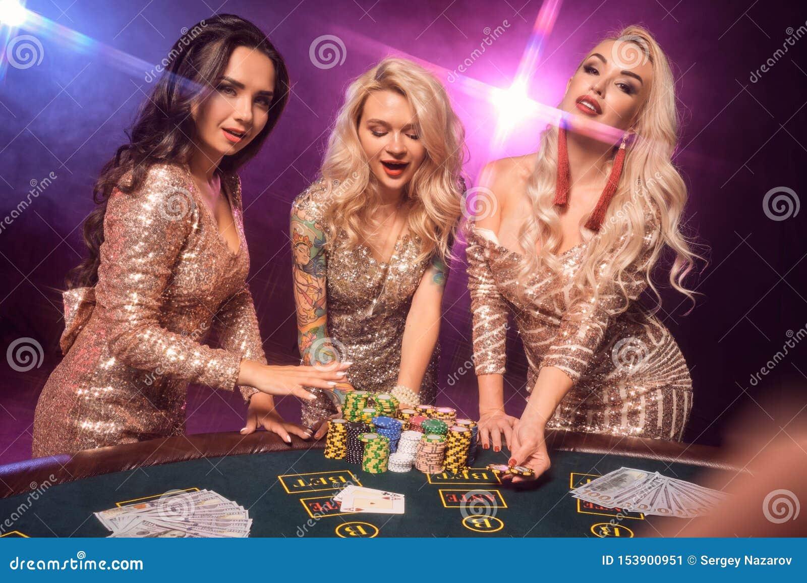 Les belles filles avec des coiffures parfaites et maquillage lumineux posent la position à une table de jeu Casino, tisonnier