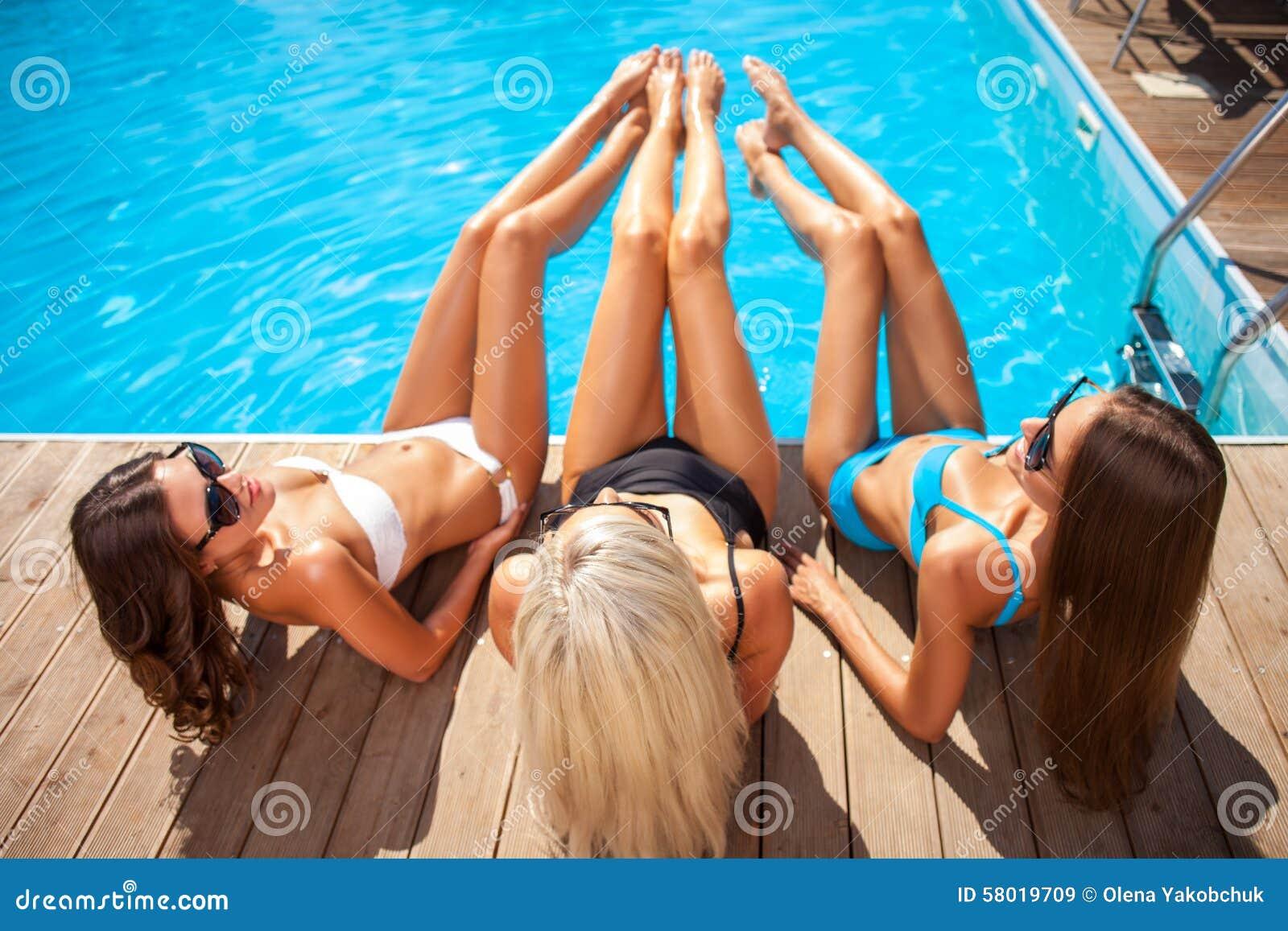 Les belles jeunes femmes les prennent un bain de soleil près de l eau