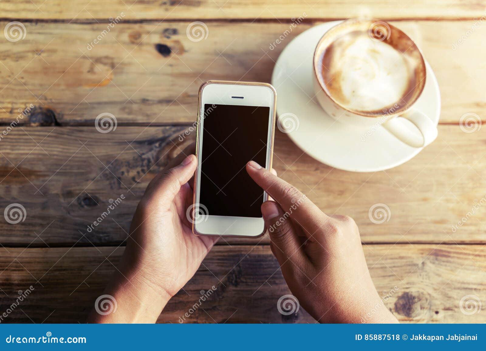 Les belles jeunes mains du ` s de femme de hippie tenant le téléphone intelligent mobile avec la tasse de café chaude au café fon