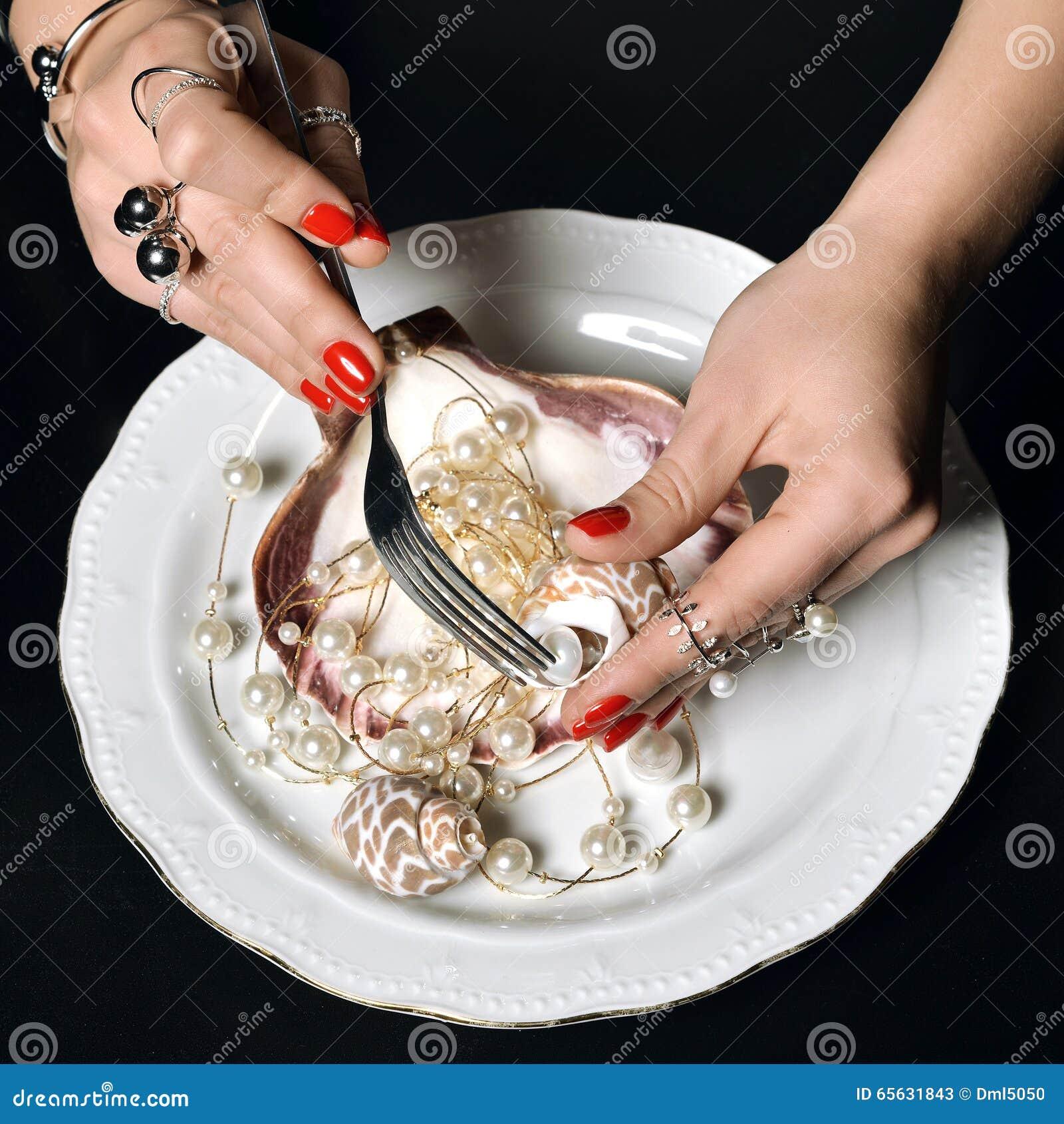 Les belles mains de femme avec le modèle rouge polissent des ongles manucurés