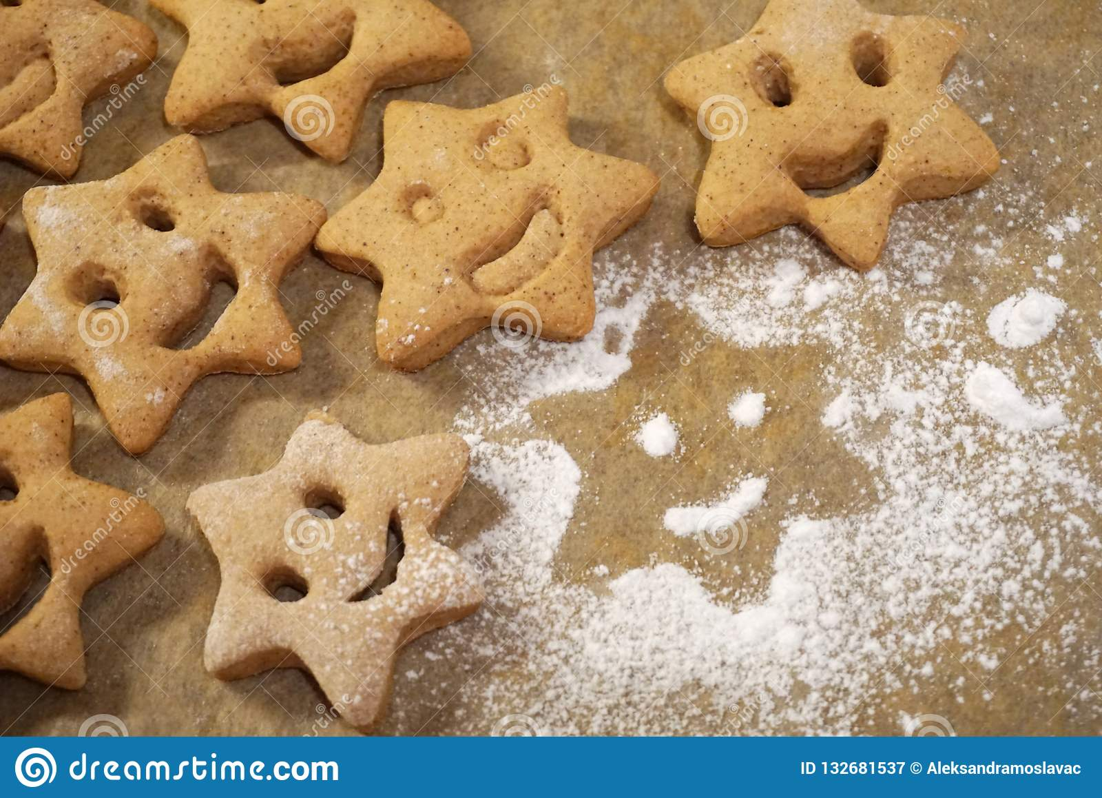 Les biscuits de Noël avec un appartement de visage de sourire s étendent sur le papier de cuisson