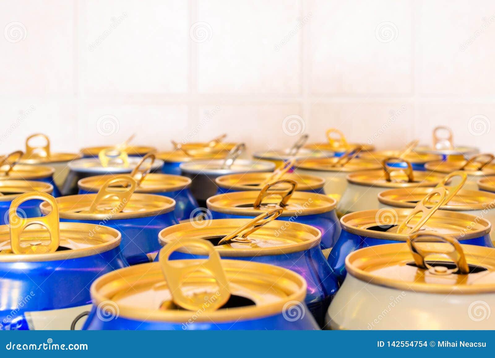Les boîtes d orangeade bleue et sur un fond carrelé, avec les séjour-sur-étiquettes se sont ouvertes Fait à partir de l aluminium