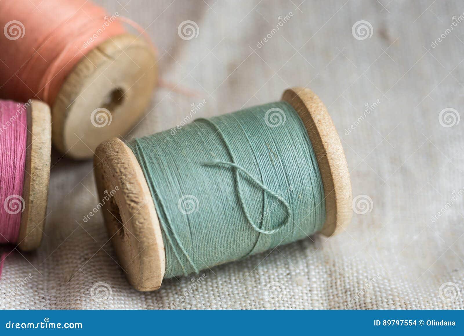 Les bobines en bois de fil de VVintage sur le tissu de toile, couleurs en pastel, plan rapproché, ont dénommé l image