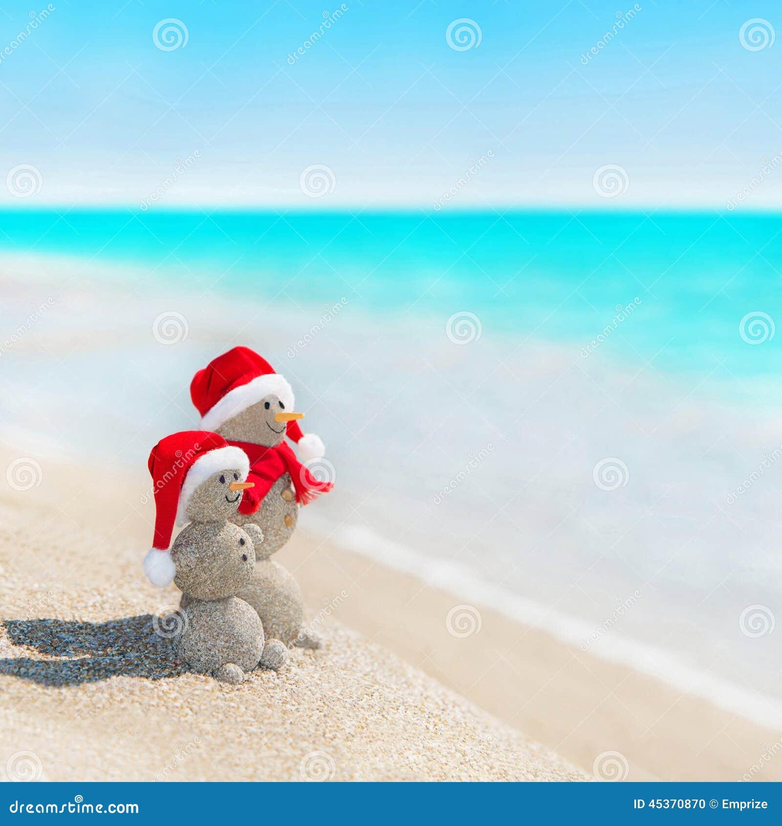 Les bonhommes de neige couplent à la plage de mer dans le chapeau de Noël