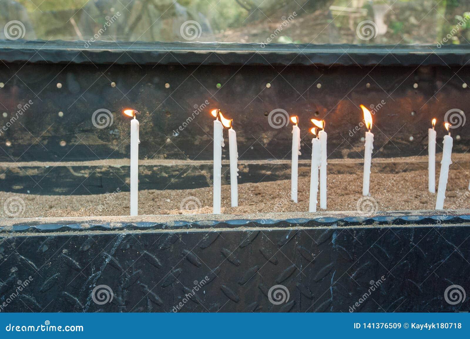 Les bougies brûlantes blanches se tiennent sur le sable