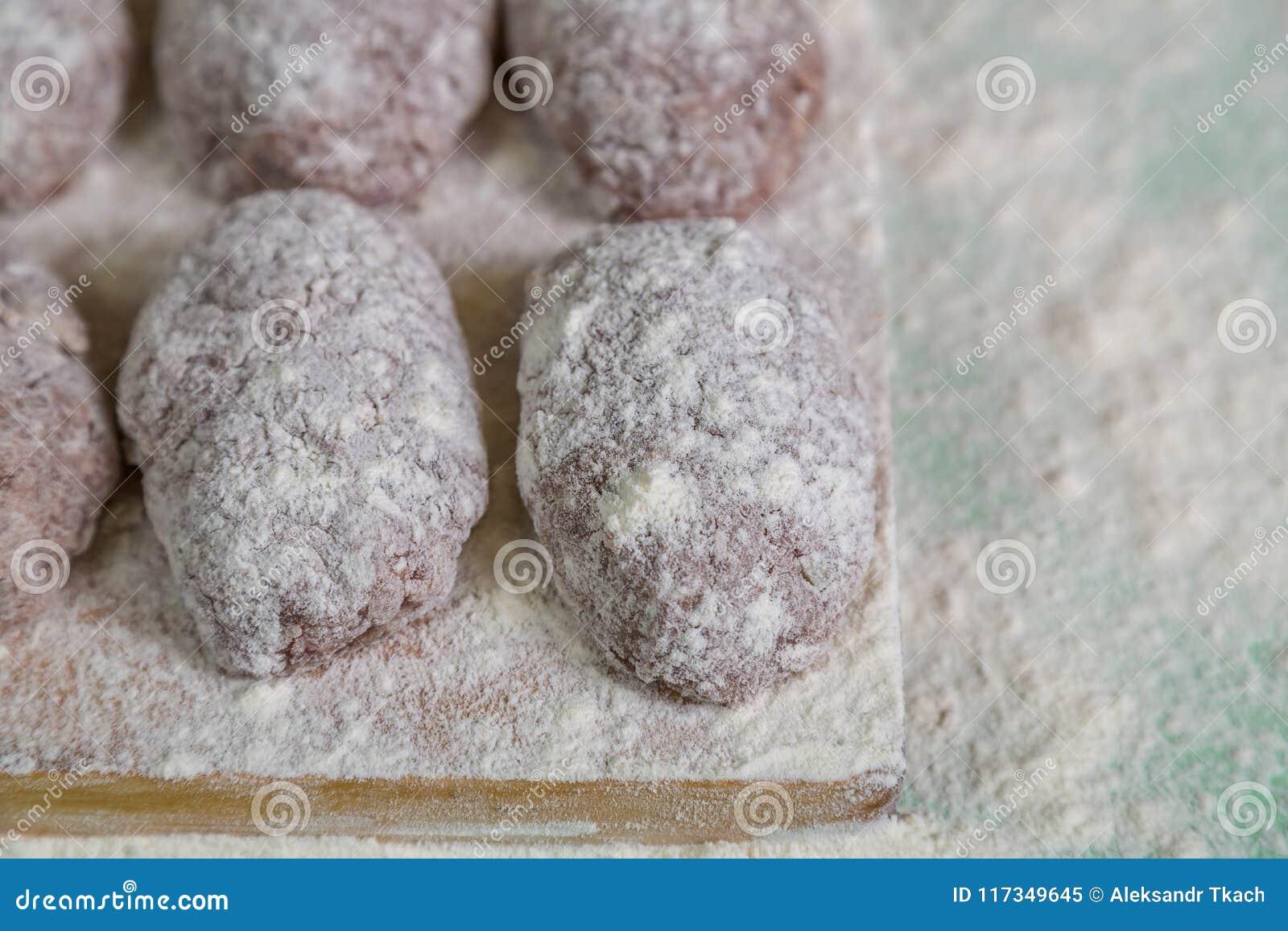 Les boulettes de viande faites maison en farine sur la planche à découper se sont préparées à la torréfaction
