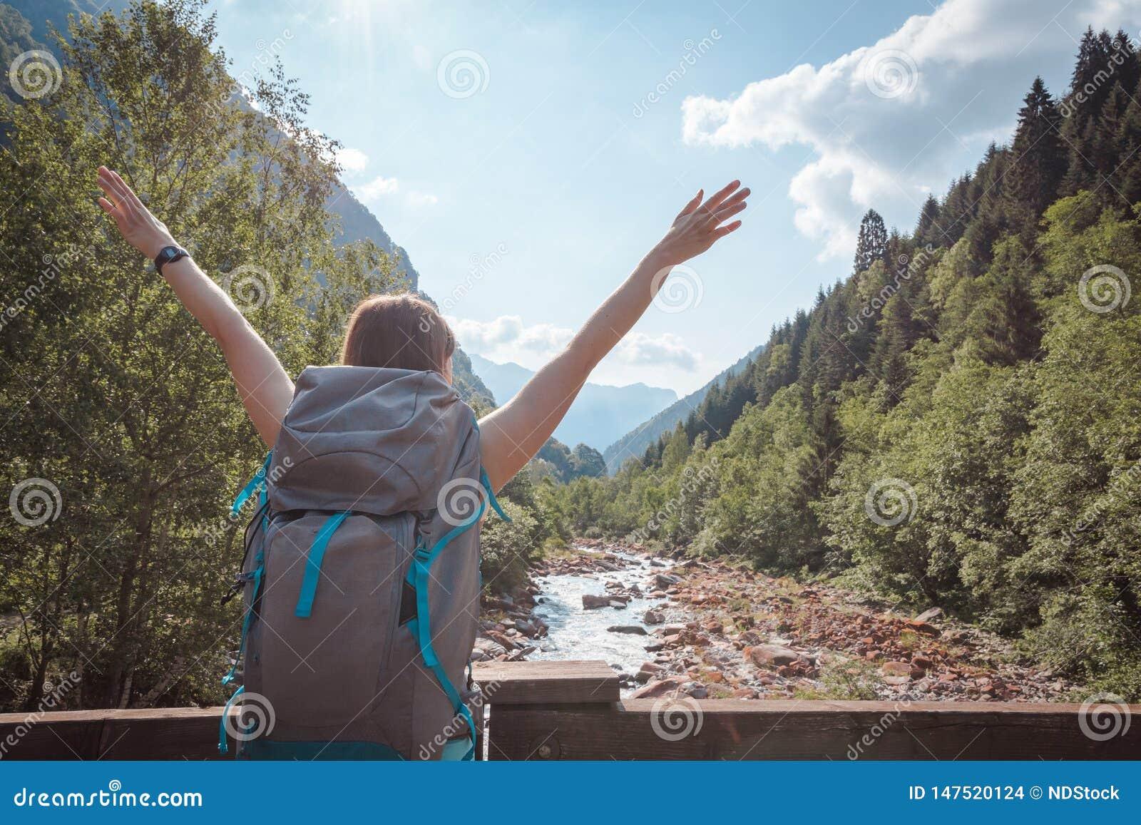 Les bras de la femme ont augmenté sur un pont traversant une rivière entourée par des montagnes