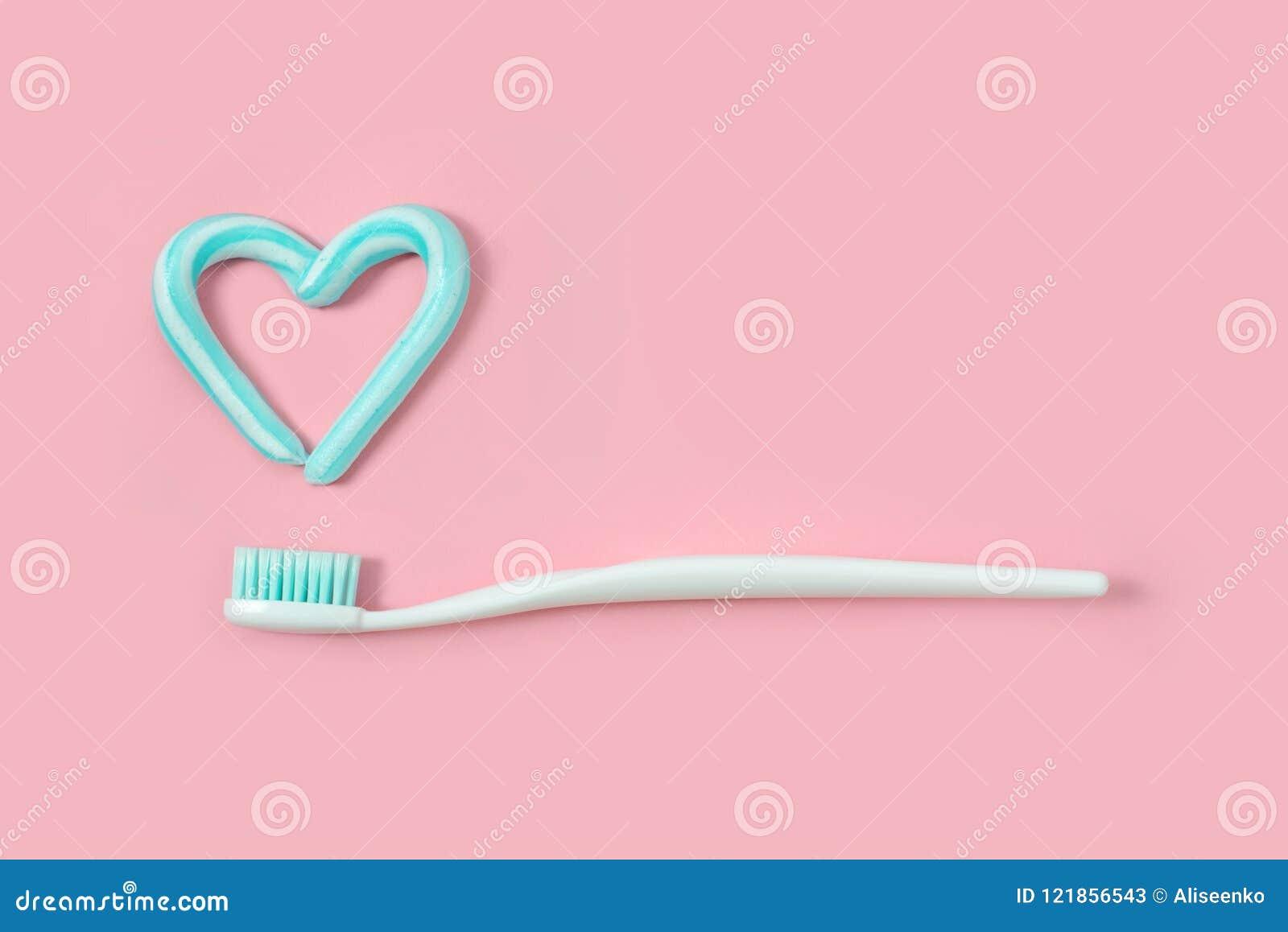 Les brosses à dents et la turquoise colorent la pâte dentifrice dans la forme du coeur sur le fond rose Concept dentaire et de so