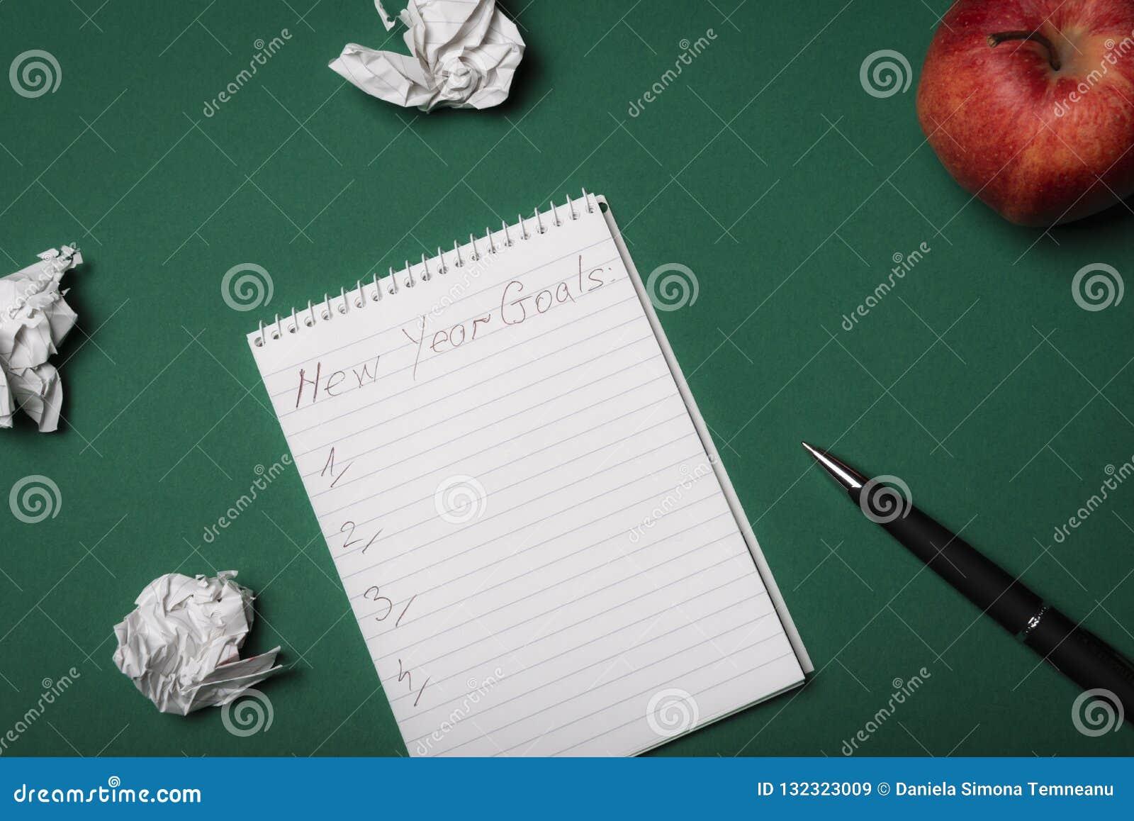 Les buts de nouvelle année énumèrent sur un carnet Au-dessus de la vue Resoluti de nouvelle année