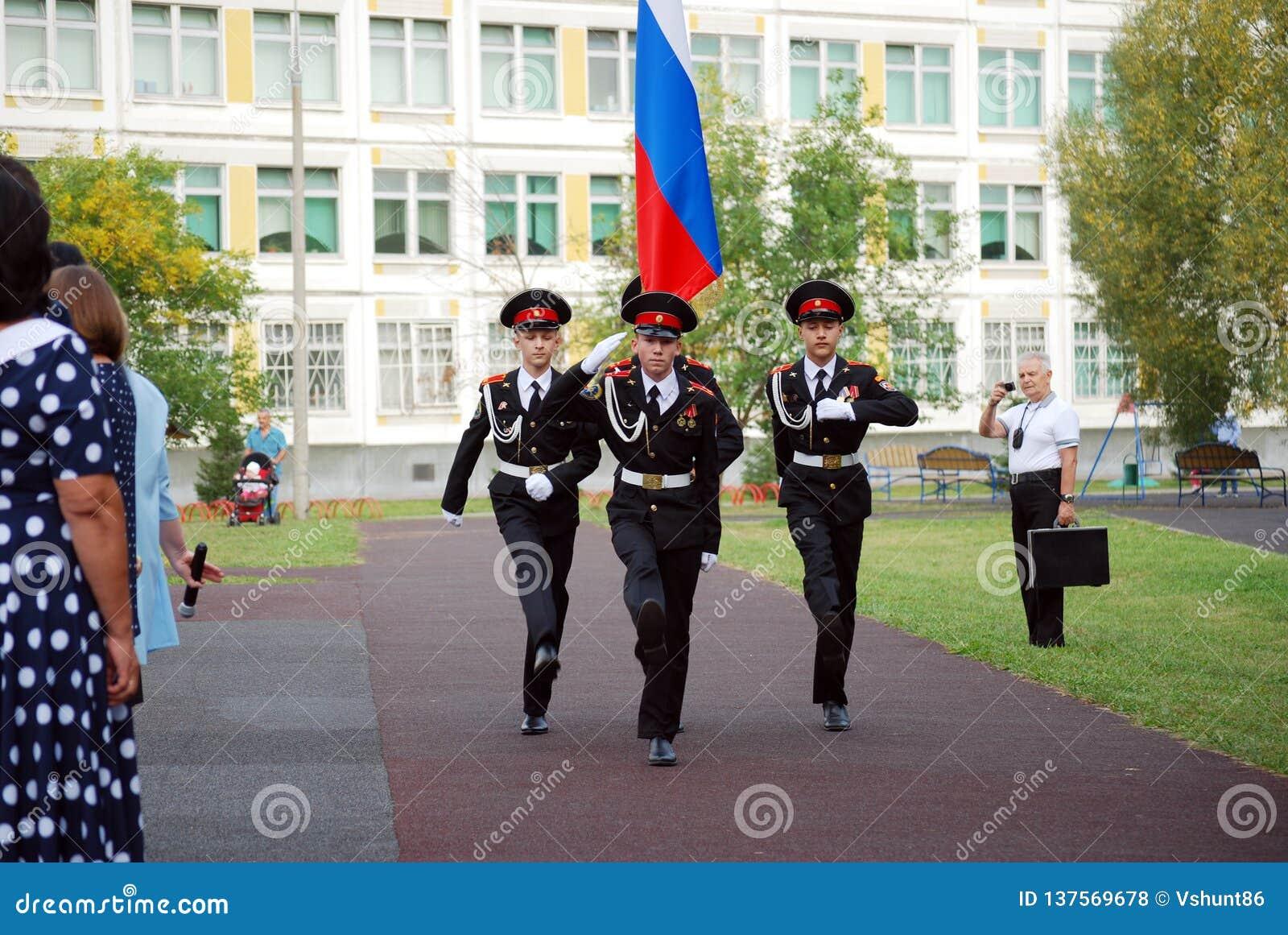Les cadets marchent avec une bannière sur une règle de matin avant école sur la défilé-terre Étudiants d école