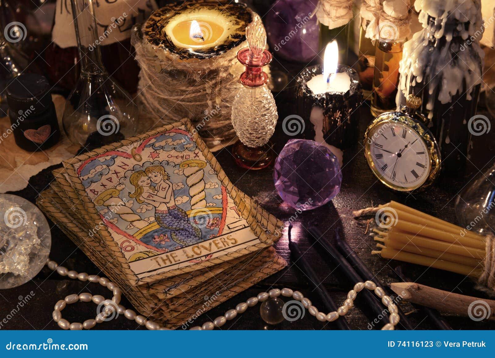 Les cartes de tarot avec le cristal, les bougies et les objets de magie