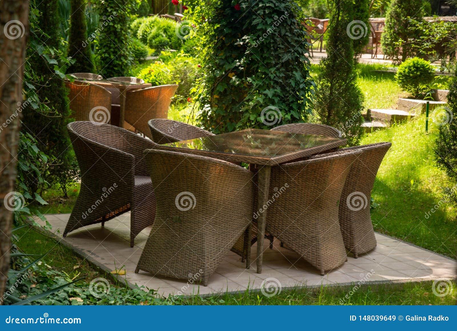 Les chaises en osier et la table sont dans le jardin pr?s des arbres