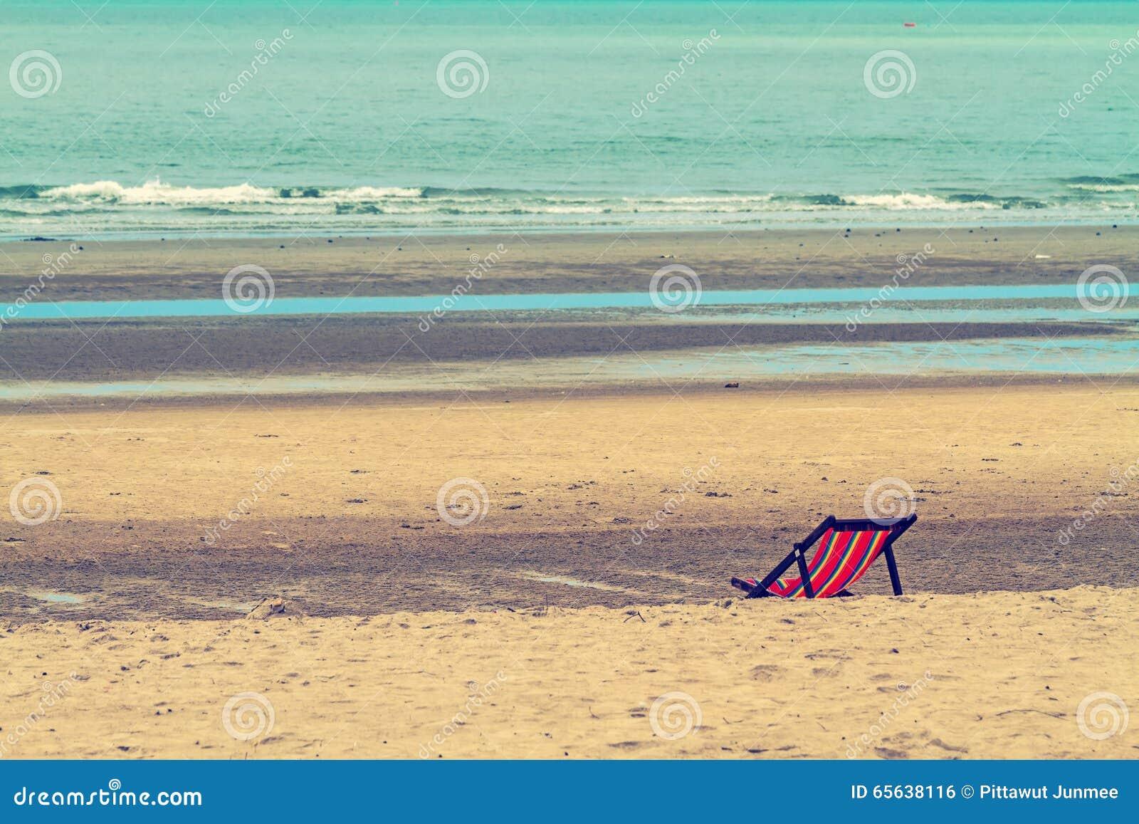 Les chaises vides sur la plage pour détendent traité dans le style de vintage