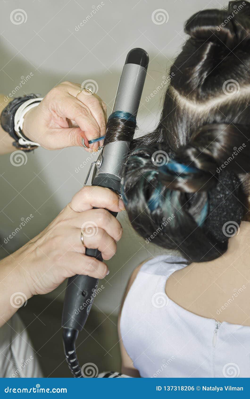 Les cheveux de la femme de bordage donnant une nouvelle coiffure au plan rapproché de salon de coiffure
