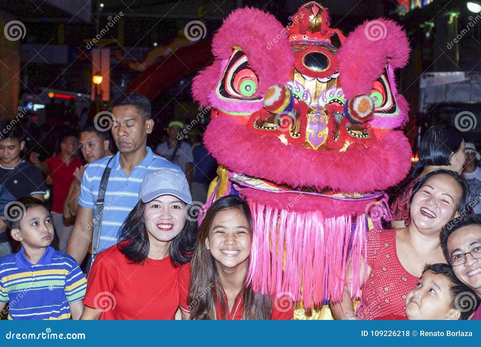 Les Chinois philippins ethniques posent avec danser Lion Mascot pendant la célébration de nouvelle année sur la rue
