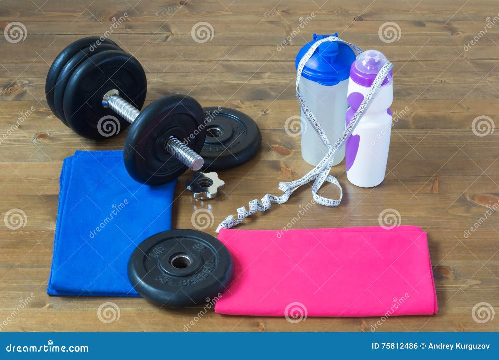Les choses pour le sport se trouvent doucement sur le plancher et l haltère se pliante