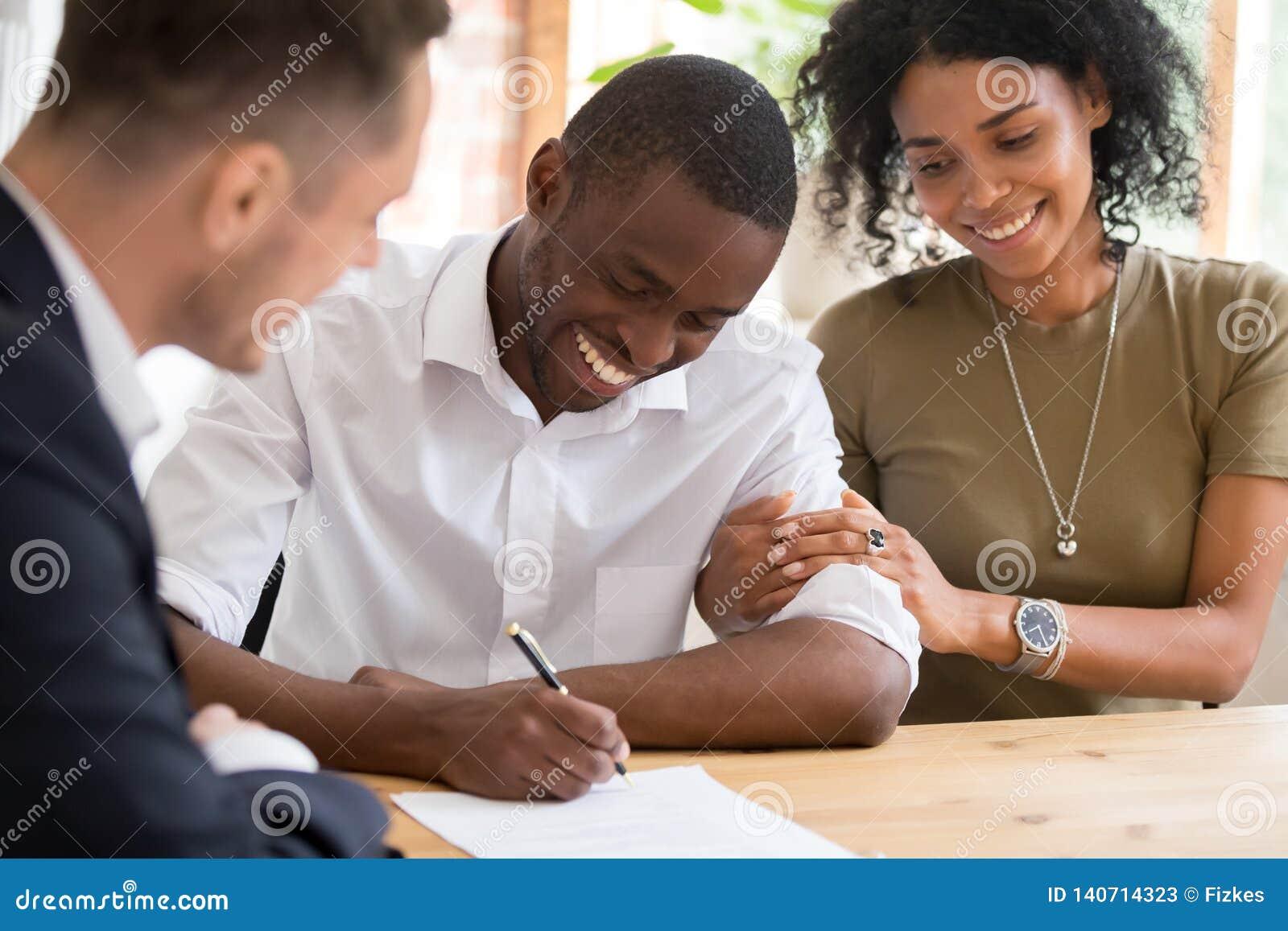 Les clients africains heureux de couples de famille signent le contrat d assurance de prêt hypothécaire