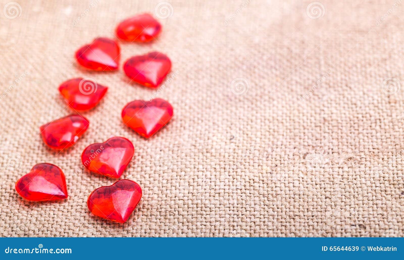 Les coeurs en verre rouges se trouvent sur une serviette de renvoyer