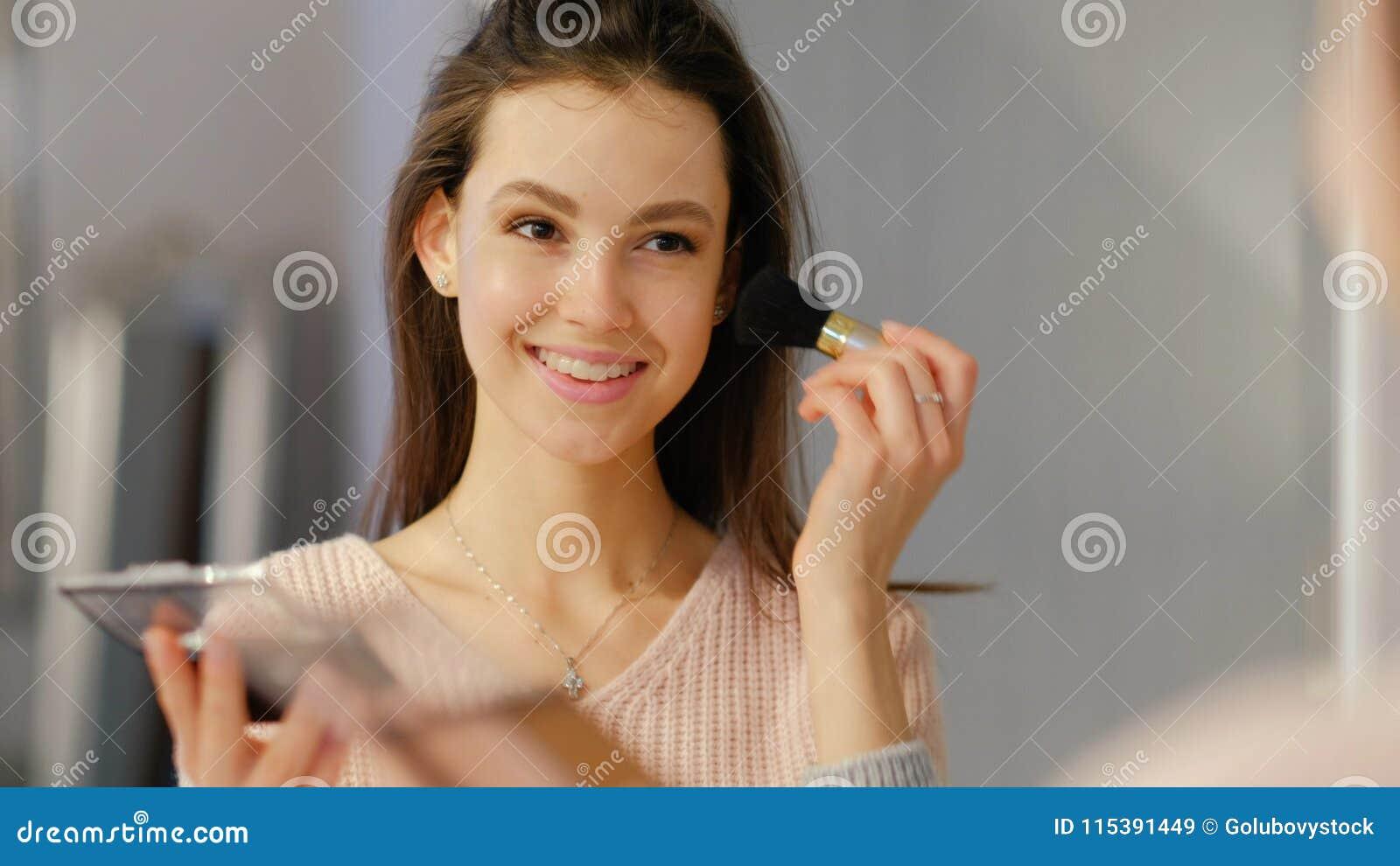 Les cosmétiques de maquillage de beauté que la fille de mode de vie s appliquent rougissent