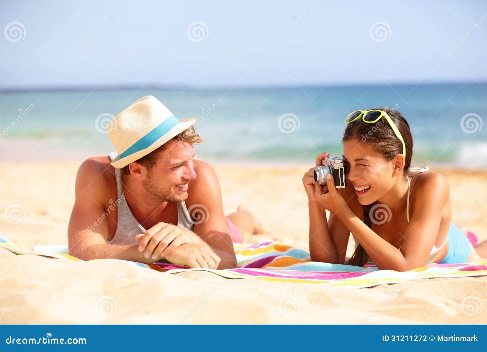 Les couples d amusement de plage voyagent - femme prenant la photo