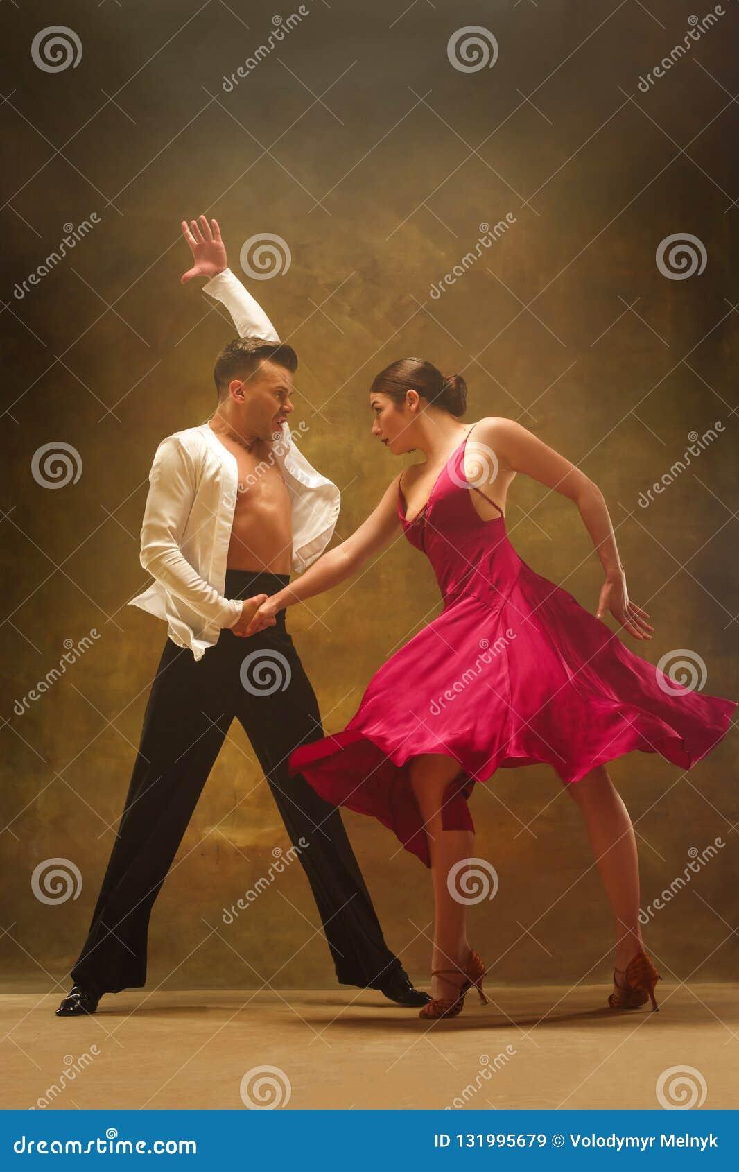 Les couples de salle de bal de danse en or habillent la danse sur le fond de studio