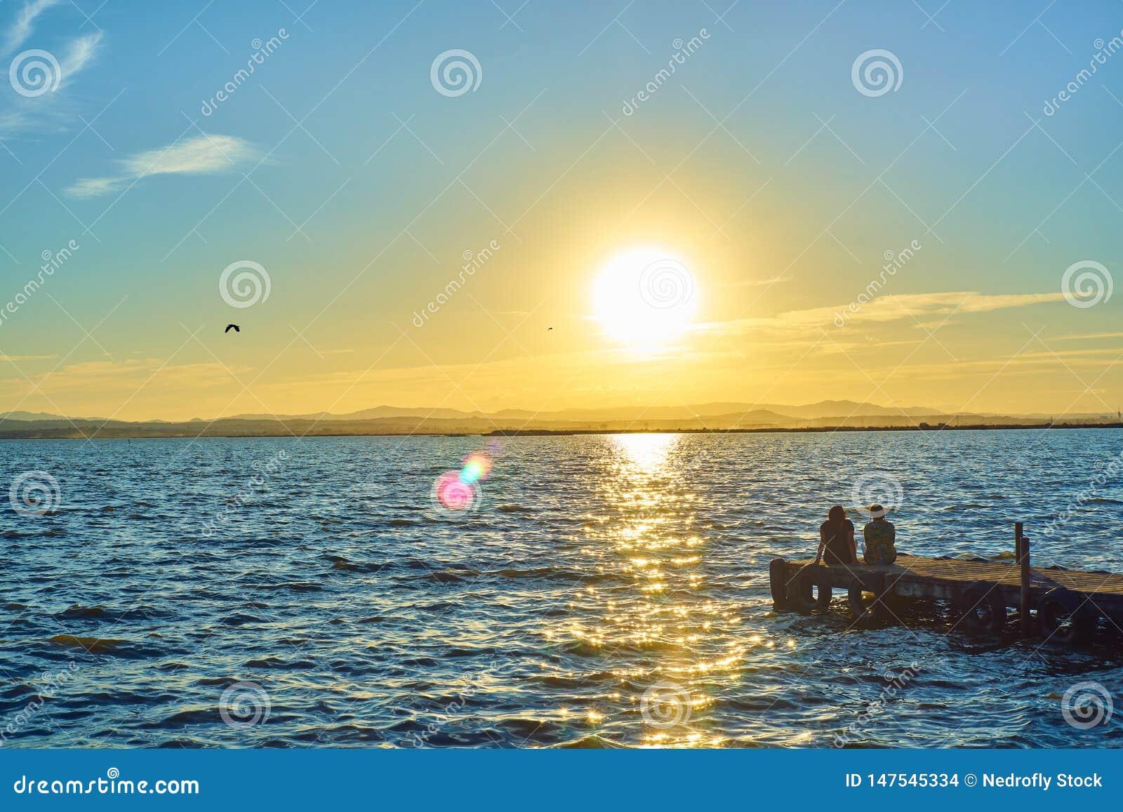 Les couples des filles contemplent le coucher du soleil se reposant sur le dock de l Albufera à Valence