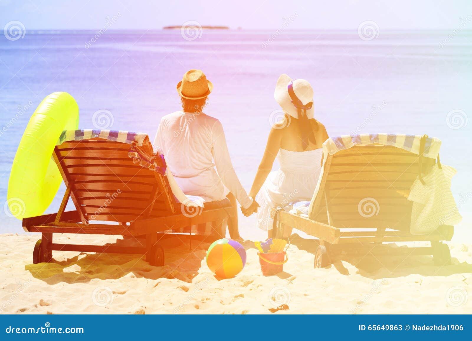 Les couples heureux détendent sur une plage tropicale de sable