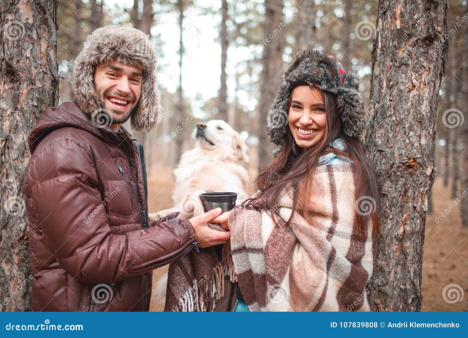 Les couples heureux passent le temps dans la forêt d automne avec un chien
